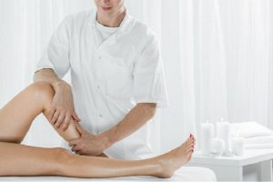 57023772 - professional masseur doing manual lymphatic drainage, light interior