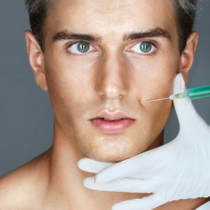 64945752 - beautiful man getting botox injection in the nasolabial folds. professional cosmetician making rejuvenate injection. beauty concept