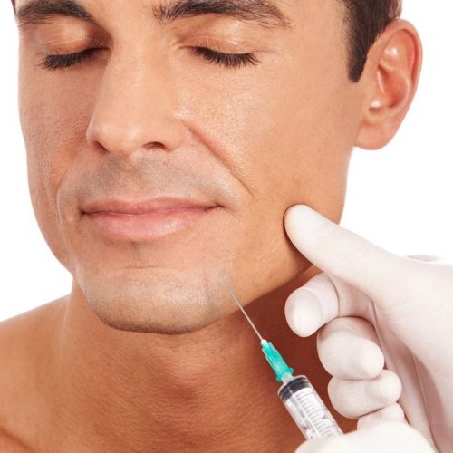 13713185 - attractive man at plastic surgery with syringe in his face