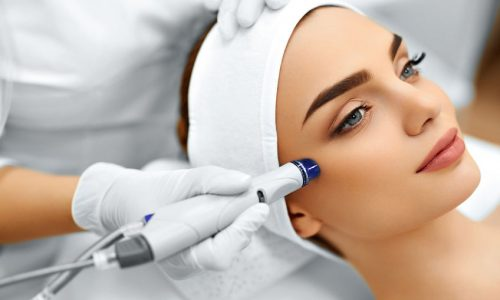 48892779 - face skin care. close-up of woman getting facial hydro microdermabrasion peeling treatment at cosmetic beauty spa clinic. hydra vacuum cleaner. exfoliation, rejuvenation and hydratation. cosmetology.