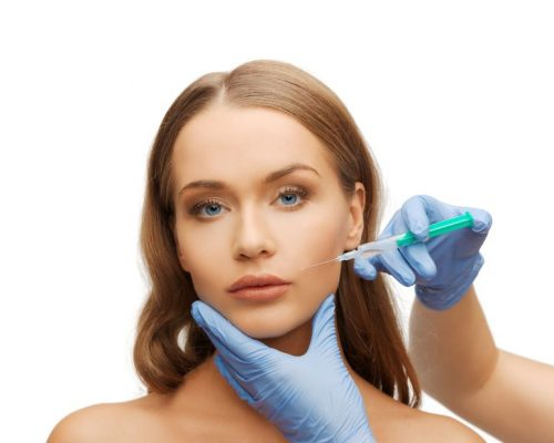 20725737 - cosmetic surgery concept - woman face and beautician hands with syringe